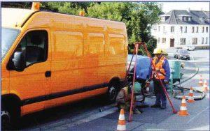 Bild zeigt AUto mit arbeitenden Männern